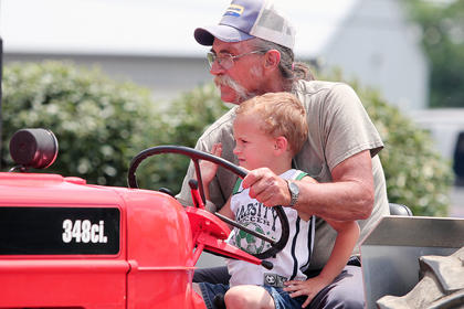 Ricky Curtsinger drives a tractor with his grandson during the parade.