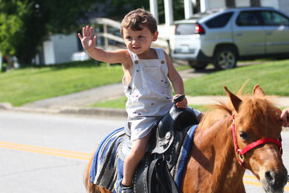 The parade's smallest participant, Charles Jewell, waves from the back of his pony.