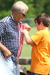 Kentucky Army National Guard veteran Steve Settles gets help with a commemorative pin from his grandson Jim Settles.